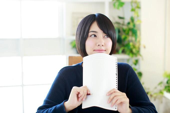 メモ紙を持って嬉しそうにする女性