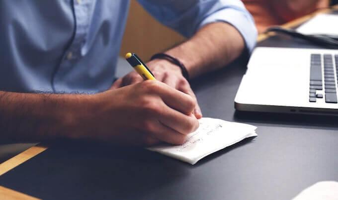 ノートにメモをする男性