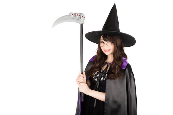 鎌を持った魔女のコスプレ女性