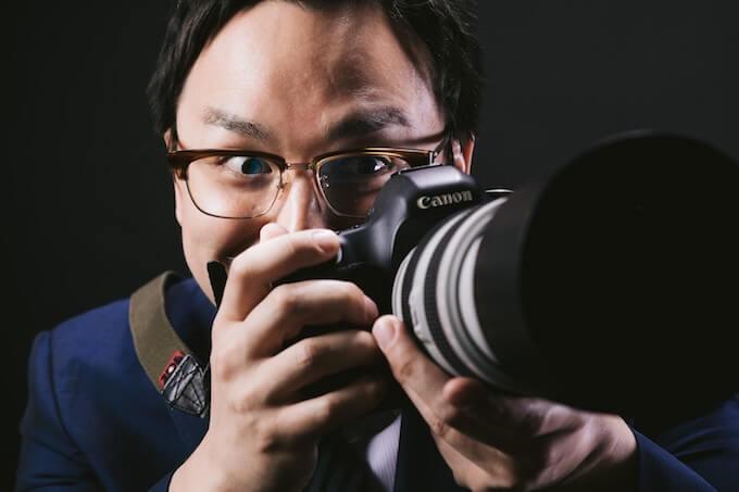 カメラを構える眼鏡の男性