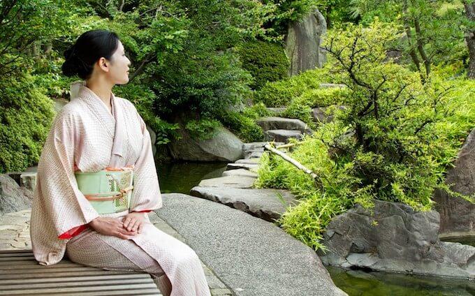 庭で休む着物の女性