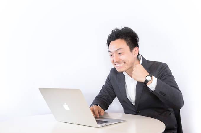 パソコンを見てガッツポーズをする男性