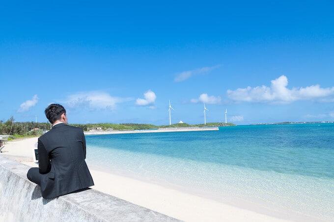 海辺でパソコンをいじる男性