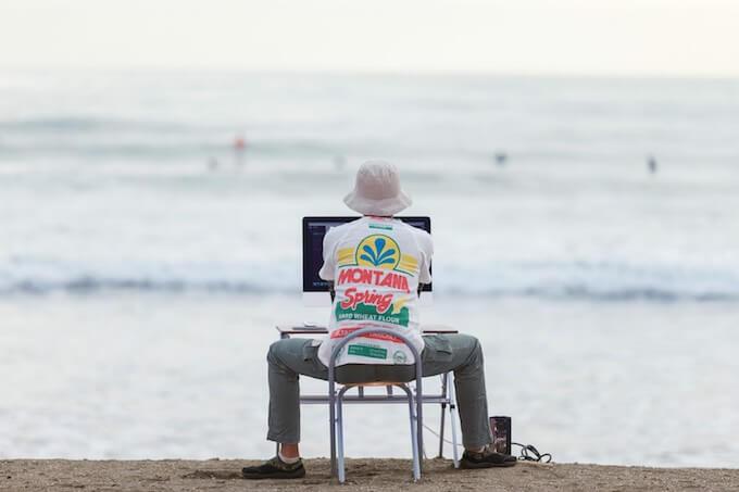 ビーチでパソコンをいじる男性