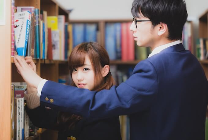 図書室にいる高校生カップル